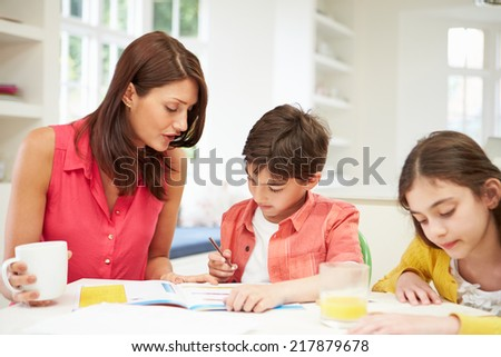 Mother Helping Children With Homework - stock photo