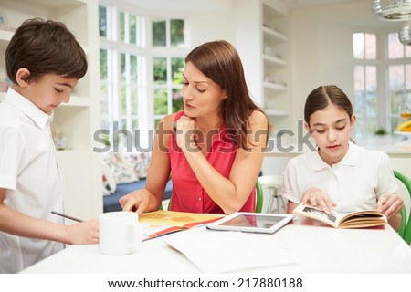 Mother Helping Children With Homework Using Digital Tablet - stock photo