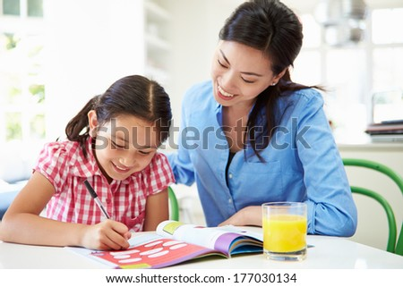 Mother Helping Daughter With Homework - stock photo