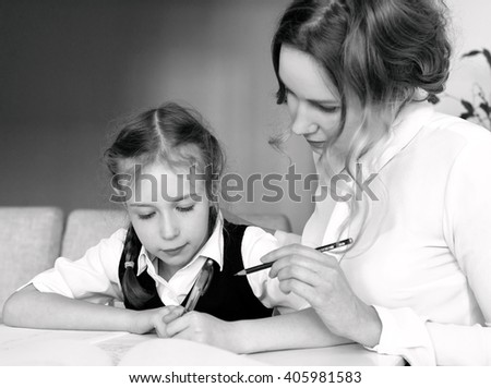 Mother helping daughter with homework at home. Black and white.