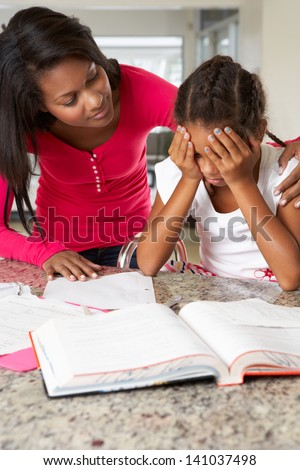 Mother Helping Daughter With Homework In Kitchen - stock photo