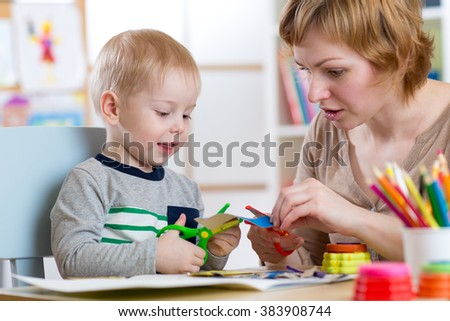 Mother helping her child to cut colored paper - stock photo