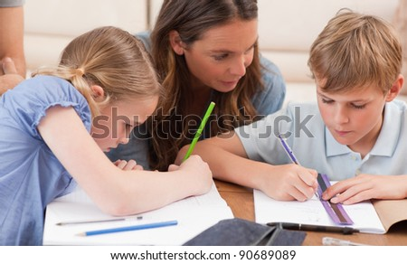 Mother helping her children to do their homework in a living room