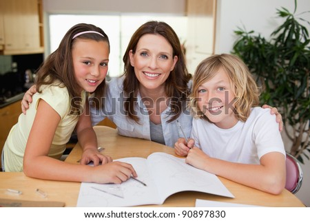 Mother helping her children with their homework