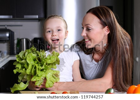 mother helping her daughter prepare salad in the kitchen