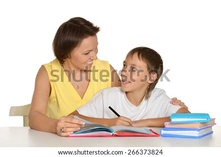 Mother helping her son doing homework on a white background - stock photo