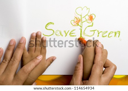 Mother helping her son for write the save green word. - stock photo