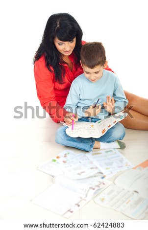 Mother helping her son with homework and making math exercises on floor in their home - stock photo