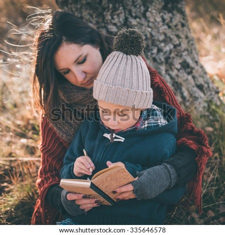 Mother helping her son writing first letters - stock photo