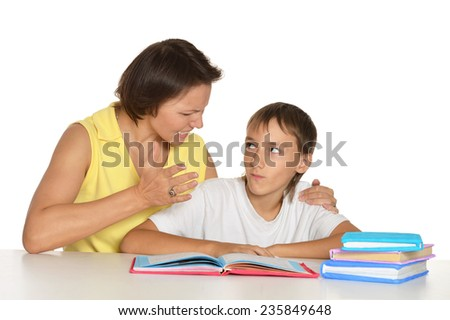 Mother helping her teen son doing homework - stock photo