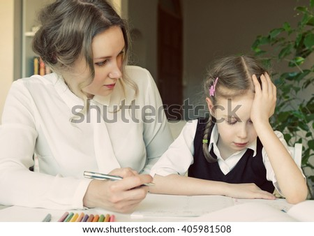 Mother helping her tired daughter with homework at home. - stock photo