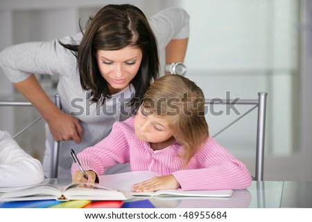Mother helping little girl to do homework - stock photo