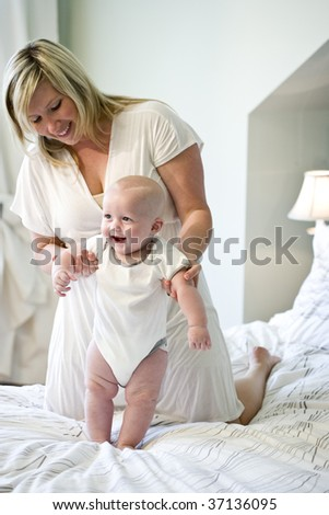 Mother helping seven month old baby learn to walk - stock photo