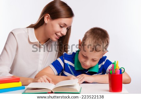 Mother Helping Son With Homework At Table - stock photo