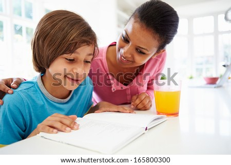 Mother Helping Son With Homework In Kitchen - stock photo