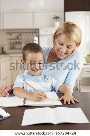 Mother helping to her son doing homework - stock photo
