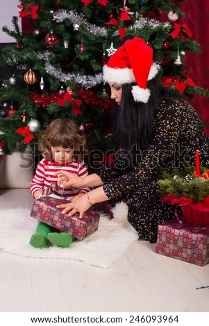 Mother helping toddler boy to open his Christmas gift - stock photo