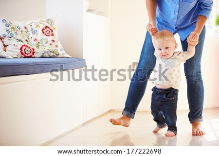 Mother Helping Young Son As He Learns To Walk - stock photo