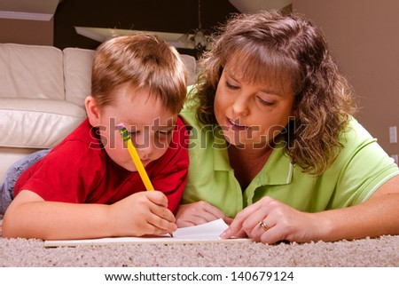 Mother helping young son with his homework - stock photo