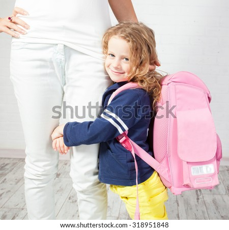 Mother helps her daughter get ready for school. Schoolgirl afraid to go to school - stock photo