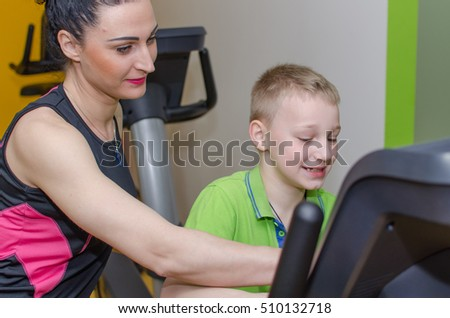 Mother helps her son with the bicycle trainer
