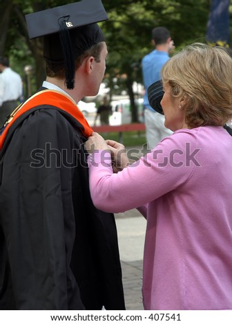Mother helps son on graduation day - stock photo