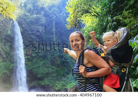Mother hold baby girl on back in carrying backpack walking in waterfall canyon. Travel adventure and hiking activity with child, active and healthy lifestyle on family summer vacation and weekend tour - stock photo