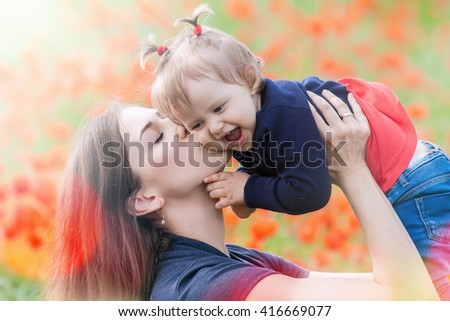 Mother holding a funny child outdoor at poppy flowers field. Happy Family Values. Baby girl and mom. Mother's care is most important in baby lfve. Mom kissing kid. Spring. ?hildren's Day, Mother's Day