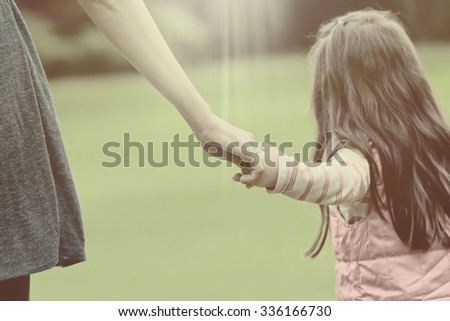 Mother holding a hand of her daughter in summer day outdoors vintage - stock photo