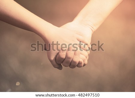 Mother holding a hand of his son in summer day outdoors