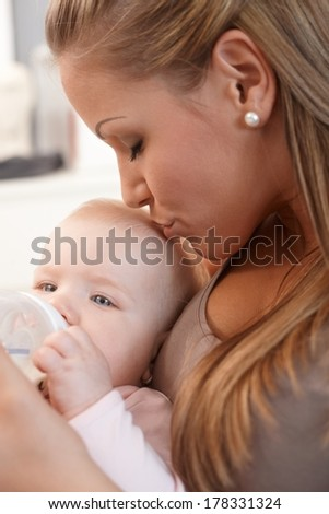 Mother holding and kissing baby daughter, feeding from nursing bottle.