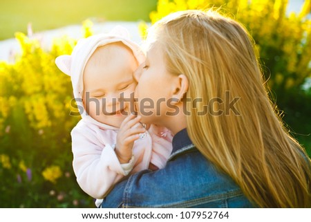 mother holding and kissing her little daughter outdoors in sunlight - stock photo