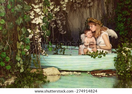 Mother holding and kissing the baby in a boat on the pond. Fairy picture angels with wings - stock photo