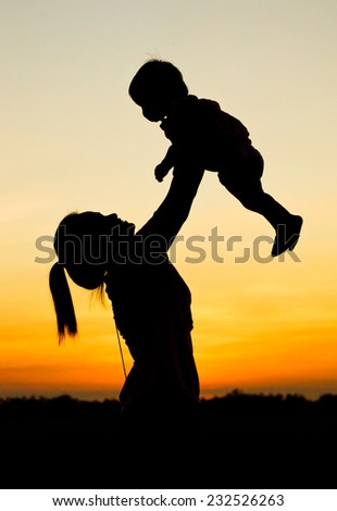 mother holding and raising her son up with sunset silhouette