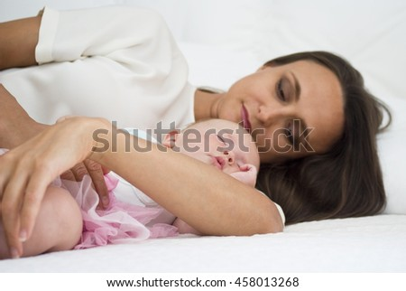 Mother holding baby daughter on bed - stock photo