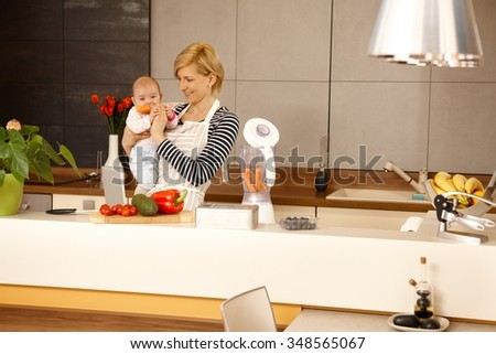 MOther holding baby girl in kitchen. Baby eating carrot.