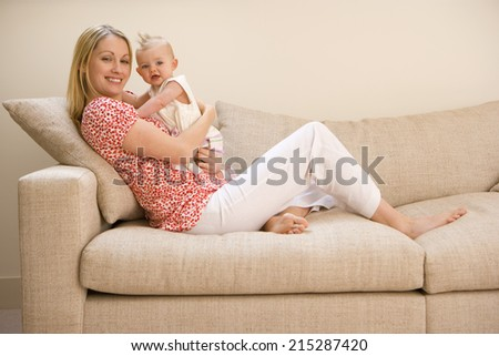 Mother holding baby girl (9-12 months), sitting on sofa, smiling, portrait