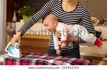 Mother holding baby in arm, ironing with the other arm. - stock photo