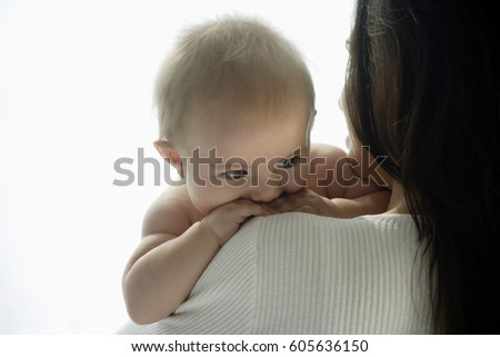 mother holding baby looking over her shoulder