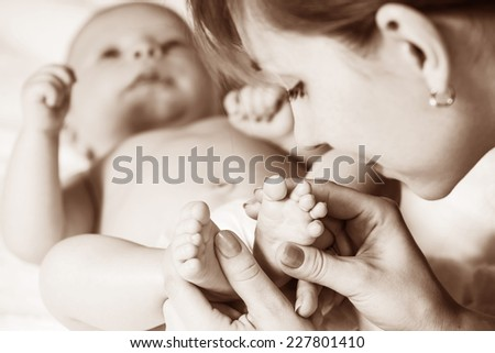Mother holding baby's feet. Close up image. - stock photo