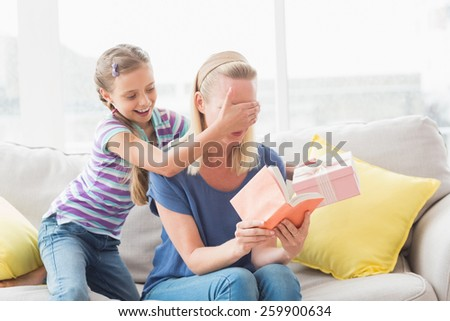 Mother holding book with daughter covering her eyes to surprise with gift at home in living room - stock photo