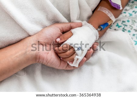mother holding child's hand who have IV solution in the hospital - stock photo