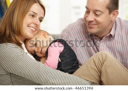 Mother holding cuddling baby girl smiling, father looking at them proudly.