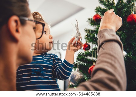 Mother holding daughter and decorating christmas tree