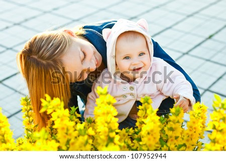 mother holding daughter near flowers in the garden and baby looking at camera - stock photo
