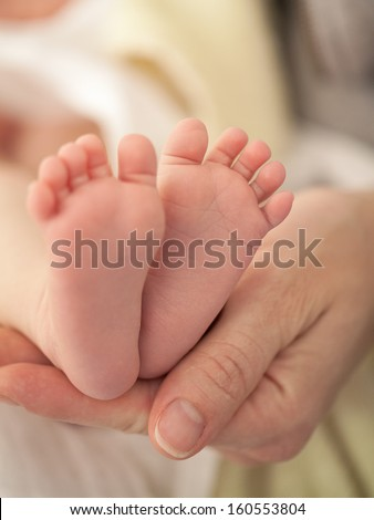 Mother holding feet of her newborn child
