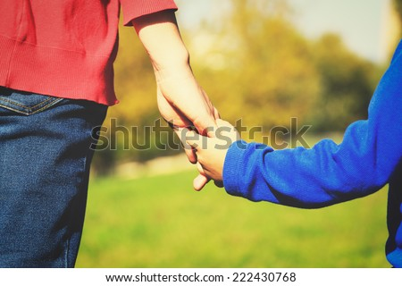 Mother holding hand of her son outdoors - stock photo