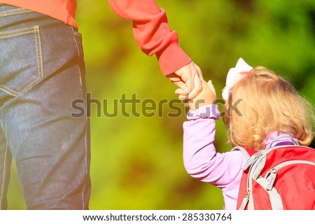 Mother holding hand of little daughter with backpack outdoors - stock photo