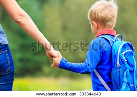 Mother holding hand of little son with backpack outdoors, back to school - stock photo