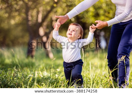 Mother holding hands of her son making first steps